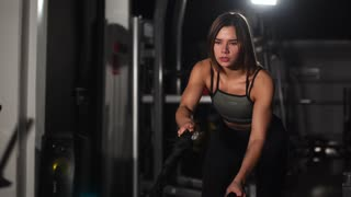 Female athlete working out with heavy ropes at the gym.
