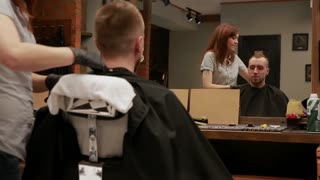Female hairdresser finished to perform a haircut. removes the Cape from the client and shows him the work done. the Steadicam shot