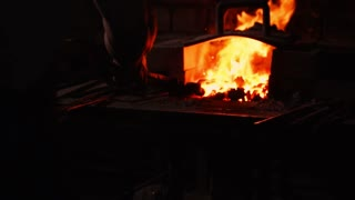 Get hot metal from the furnace to make an arrow tip. Hammer blows on the hot metal. Sparks of metal flying in all directions, slow motion. Ancient craftsmanship.