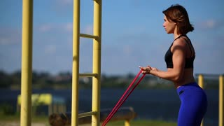 Girl on the nature doing exercises on the biceps with elastic bands. Sports outdoors near the river