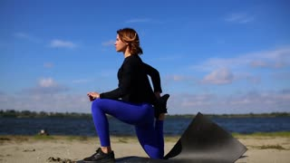 Girl on the river Bank performs the stretching and relaxation of the muscles after a hard workout. Fitness and yoga outside near the beach