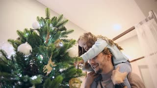 Girl sits at daddy on the neck and they decorate the Christmas tree