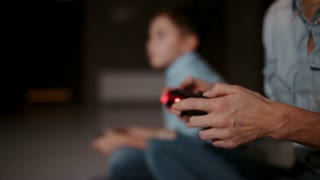 Hands holding a controller to a game console, and in the background the boy looks at the faucet and playing video games. The focus shifts from one to another