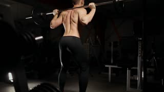 Handsome muscular man exercise squats in the gym