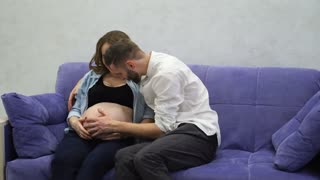 Happy couple sitting at home laughing and hugging each other, woman is pregnant and the man communicates with the baby through the abdomen.
