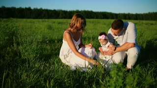 Happy family. Dad mom and a little girl, walking in a field dressed in white under the rays of the setting sun