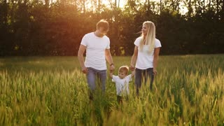 happy family, mom dad and son on an emotional walk. Running and enjoying life in a green field in the fresh air, blue sky, nature