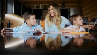 Happy family mother of two children helps the sons to do their homework sitting at the big table in the kitchen