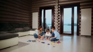 Happy mother with two children sitting on the floor of his country house spending time together collecting children's designer. Living room with panoramic Windows