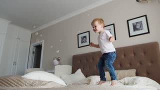 Jumping off of happiness on the bed looking at flying soap bubbles