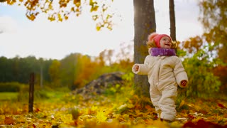Little girl in autumn clothing in warm hat and scarf standing in the Park watching the yellow leaves falling off the trees. Lifts and separates the leaves from the tree