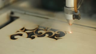 Machine for laser cutting wood close up cuts chipboard and the smoke appears. The red beam