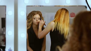 make up artist applying make up on model
