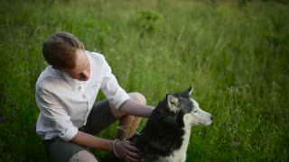 Man and dog Siberian huskies concept. Asian young man with his dog on meadow