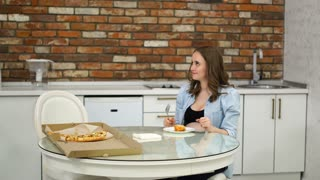 Man and pregnant woman eating pizza at home in their kitchen. Poor diet. Fatty foods. Obesity