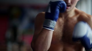 Man with Boxing gloves Boxing in front of the camera close up. Close-up of young man punching. Boxer performing uppercut