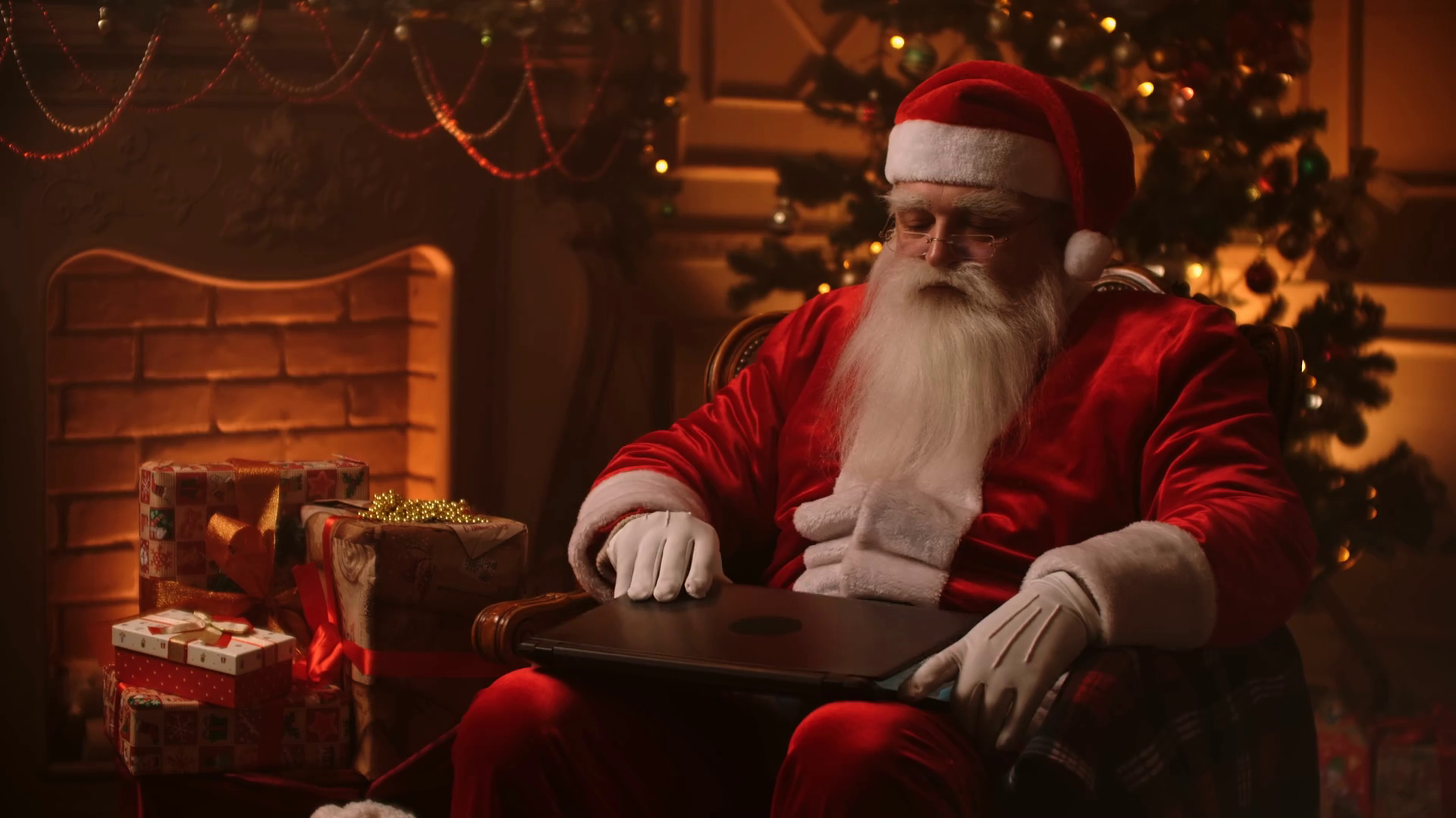 Modern Santa Claus Cheerful Santa Claus Working On Laptop And Smiling While Sitting At His Chair With Fireplace And Christmas Tree In The Background Stock Video Footage Storyblocks