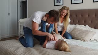 Mom and father tickling her child. people, family, fun and morning concept - happy child with parents tickling in bed at home. Happy family spending time together in bedtime playing and hugging