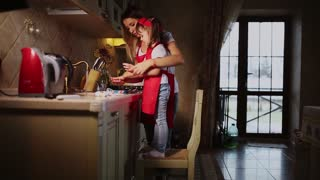 Mom helps to wash the hands of his daughter in the kitchen after cooking dinner