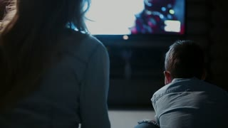 Mom with son in front of the TV playing video games and pass each other the joystick. Rear view of the TV screen
