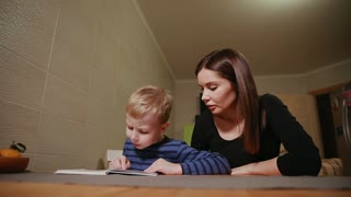 Mother and son sitting in the kitchen of his house and learning to read book