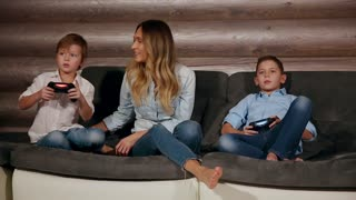 Mother and two sons sitting on the sofa in his house playing video games with wireless joystick. Happy people in the house