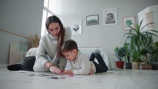 Mother with a child in the white interior of his home to collect the jigsaw puzzle together with his young son. Happy family, educational games