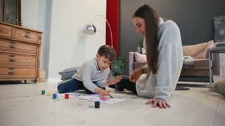 Mother with a child in the white interior of his house was opened the paint can sitting on the floor and dip your fingers in paint and draw on paper with your hands. Happy family