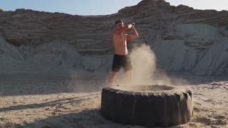Muscle athlete strongman man hits a hammer on a huge wheel in the sandy mountains in slow motion at sunset. The dust from the wheels rises.