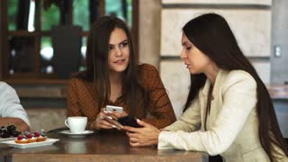One-on-one meeting. Two young business women sitting at table in cafe. Girl shows her friend image on screen of smartphone. On table is closed notebook. Meeting friends.