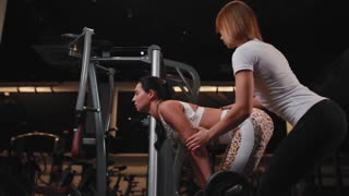 Personal female trainer in white t-shirt helps to do the exercise deadlift female female client with long dark hair. Exercising in a gym