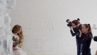 Photographers in the master class photograph the bride in the style of a boho. In the photo studio