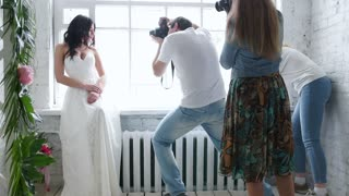 Photographers photographing a beautiful brunette bride model. In a wedding dress in a master class. The girl is posing by the window. Photographs are trained