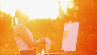 Portrait of a girl with white hair in a white t-shirt, depicting a landscape on canvas in sunset in the sun using oil paint and brush