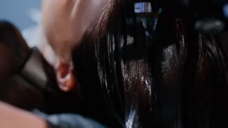 Portrait of women which washes her hair in a beauty salon. Hair stylist at work - hairdresser washing hair to the customer before doing hairstyle