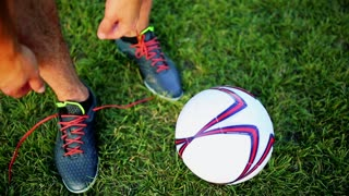 Professional football player at practice tying laces in the boots. Close-up with the ball