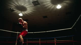Professional pumped-up fighter in a boxing ring in red sherds and boxing gloves holds a fight with a shadow on a dark background
