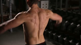Rolled man with rippling muscles performing exercises for shoulders with dumbbells in the gym