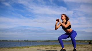 Runner woman stretching legs with lunge hamstring stretch exercise leg stretches. Fitness female athlete relaxing on beach doing a warm-up before her strength training cardio workout