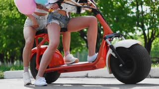 Sexy girls with sweet cotton in short shorts ride an electric scooter in the Park
