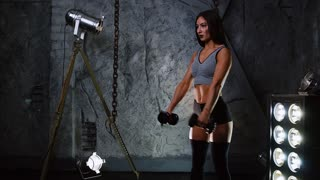 Sexy sporty girlfriend, fitness model doing exercises for the shoulders lifting the dumbbells in front of a side view.