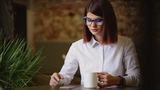 Simpatic brunette with glasses close-up. Drinks fragrant coffee and using a mobile phone dials up text messages, watches news, flips through photos, communicates in a social network