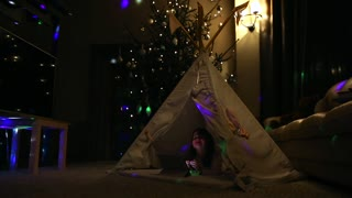 Sitting at home in a tent against the background of a Christmas tree a little girl lying on the floor talking on video communication, learning to use a tablet computer