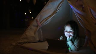 Sitting at home in a tent against the background of a Christmas tree, a little girl lying on the floor watching cartoons, smiling with teeth and laughing out loud
