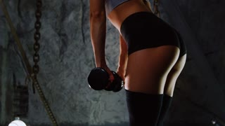 Slender sexy athlete performs slopes down with dumbbells in short shorts. Exercises to strengthen the muscles of the hips. Slim sexy athlete performs tilts down with dumbbells