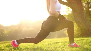 Slim athletic woman working out in park doing knee-bounce exercise or lunges. Sunset feet close up in pink sneakers on the grass