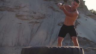 Sport Fitness Man Hitting Wheel Tire With Hammer Sledge Cross fit Training,