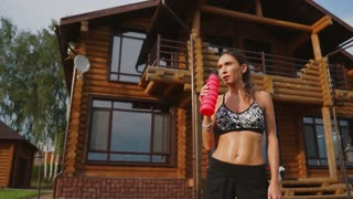 Sports woman with a beautiful press in a black top on the background of a wooden mansion after a workout drinking water from a bottle.