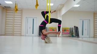 Star Inversion aerial antigravity yoga pose, woman exerciseses with hammock