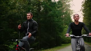 Steadicam shot of mountain biking couple riding on bike trail at sunset doing high